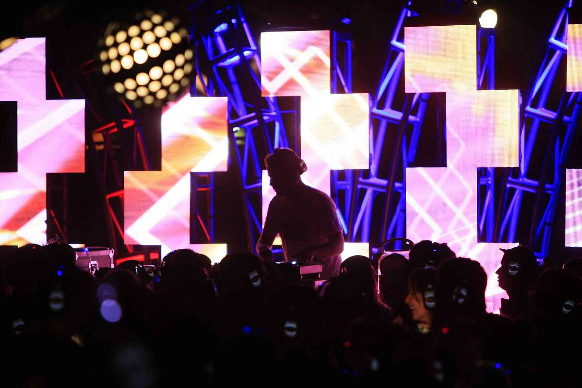 A DJ mixes music at Silent Frisco, a dance party where all participants listen to the music through headphones, during the Treasure Island Music Festival on Treasure Island in San Francisco, Calif. Sunday, October 19, 2014