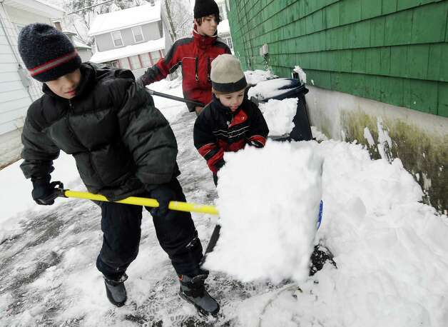 Brothers, Ted, age 10, left, Nick, 11, in back center, and Greg, age 4, right, of the Van Kampen family of Glenwood Rd. in  Menands working together to shovel the driveway of their home on Wednesday, Dec. 9, 2009, in Menands, NY.  A winter storm hit the region forcing the dig out, school & activity cancelations and traffic jams. Photo: LUANNE M. FERRIS, TIMES UNION / 00006743A