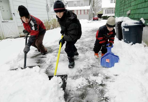 Brothers, Nick, 11, left, Ted, age 10, in center, and Greg, age 4, right, of the Van Kampen family of Glenwood Rd. in Menands working together to shovel the driveway of their home on Wednesday, Dec. 9, 2009, in Menands, NY.  A winter storm hit the region forcing the dig out, school & activity cancelations and traffic jams. Photo: LUANNE M. FERRIS, TIMES UNION / 00006743A