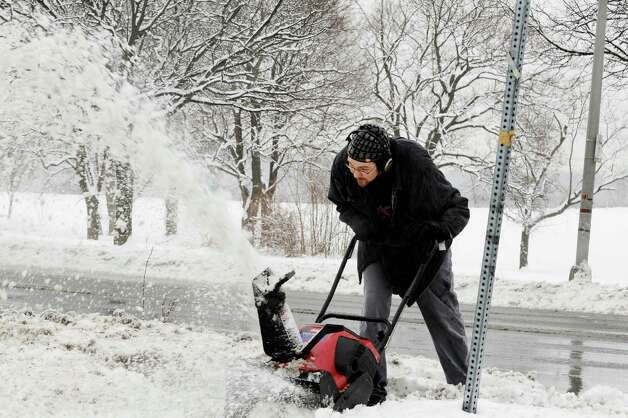 Corey Orlop, of Menands leans over to push his snow blower at the corner of Glenwood Rd. and Rt. 32, near his home on Wednesday, Dec. 9, 2009, in Menands, NY.  A winter storm hit the region forcing the dig out, school & activity cancelations and traffic jams. Photo: LUANNE M. FERRIS, TIMES UNION / 00006743A