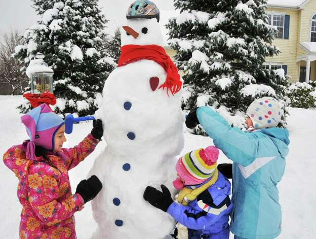 """Sisters, Heidi, 9, left, Molly, 7, and Mary Beth( at right) Zahnlenter build a 7-foot snowman in the front yard of their Clifton Park Home Wednesday afternoon December 9, 2009.  """"Dad helped."""" Photo: John Carl D'Annibale, Times Union"""