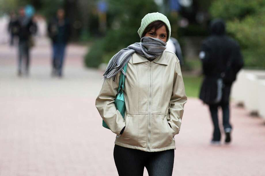 San Antonio College student Fernanda Ramos uses a scarf to ward off the cold winds while going between classes on Thursday, Nov. 13, 2014. A cold front with a stiff wind brought temps into the 30s during the morning hours. Photo: Kin Man Hui, San Antonio Express-News / ©2014 San Antonio Express-News