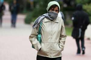 San Antonio College student Fernanda Ramos uses a scarf to ward off the cold winds while going between classes on Thursday, Nov. 13, 2014. A cold front with a stiff wind brought temps into the 30s during the morning hours.