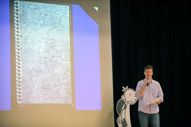 Jeff Kinney, author/illustrator of the Diary of a Wimpy Kid books, talks about his journey to becoming an author during a book tour stop at Skano Elementary School Thursday, Nov. 13, 2014, in Clifton Park, N.Y.  On the screen is a photo of a notebook Kinney used to write down funny ideas before he started writing the first book.  (Paul Buckowski / Times Union) Photo: Paul Buckowski / 00029458A