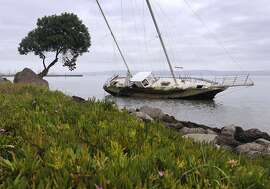 An abandoned 35-foot sailboat remains stuck in the muddy bay shore at Oyster Point in South San Francisco, Calif. on Wednesday, Nov. 12, 2014.