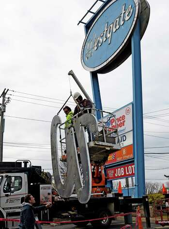 Antonio Flores, left, and David Delano of Saxton Sign Company lower the W from the sign in front of the Westgate Shopping Center Thursday afternoon Nov. 13, 2014 in Albany, N.Y.  The landmark sign is being dismantled for renovation.   (Skip Dickstein/Times Union) Photo: SKIP DICKSTEIN / 00029464A