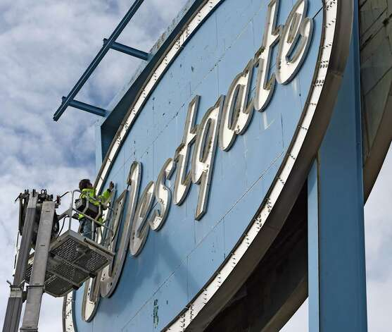 Antonio Flores of Saxton Sign Company prepares to lower the W from the sign in front of the Westgate Shopping Center Thursday afternoon Nov. 13, 2014 in Albany, N.Y.  The landmark sign is being dismantled for renovation.   (Skip Dickstein/Times Union) Photo: SKIP DICKSTEIN / 00029464A