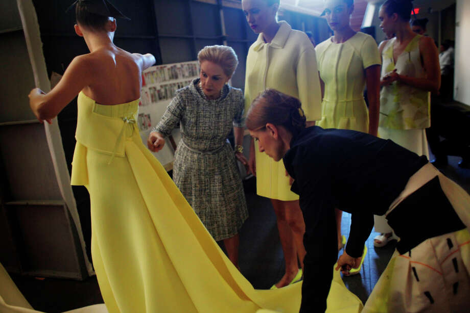 """The """"Art of Fashion"""" Carolina Herrera fashion show at the de Young Museum on Nov. 3 had lots of drama onstage, but behind the scenes, there was a similarly intense story. The show took almost a year to put together, but lasted only 12 minutes on the runway. Here, Herrera adjusts a gown before it hits the runway. Photo: Lea Suzuki / The Chronicle / ONLINE_YES"""