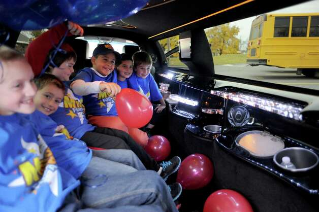 Nikos Johnson, center with balloon,  a third grade student at Jefferson Elementary School gets picked up from school by limo with five of his friends after winning the First New York Federal Credit Union's Millionaire for the Day on Thursday Nov. 13, 2014 in Rotterdam, N.Y. First New York Federal Credit Union has been teaching thousands of area students for years to save their money through its KID$ (Keep Investing Dollars Savings) Program. To celebrate the studentsa€™ success, the credit union randomly selected a school banker to be treated like a Millionaire. As the Millionaire for the Day, Nikos Johnson and his classmates will be treated to a waiter-served lunch. In addition, Nikos and five of his friends will be picked up from Jefferson Elementary School at dismissal time and the red carpet will be rolled out treating them to a limousine ride to First New York Federal Credit Uniona€™s headquarters at 2 Wall Street, Albany where they will meet the President/CEO, Lucy Halstead and members of the Board of Directors, receive a personal tour of the credit union and return home via limousine at the end of the day. Mr. Joby Gifford, Principal at Jefferson Elementary School. Nikos, like many other students at Jefferson Elementary School make deposits each week from money they have earned by doing chores, receiving allowance and birthday money. Some students deposit money into their savings account from the soda bottles they help return, while others often find money on the ground. (Michael P. Farrell/Times Union) Photo: Michael P. Farrell / 00029474A