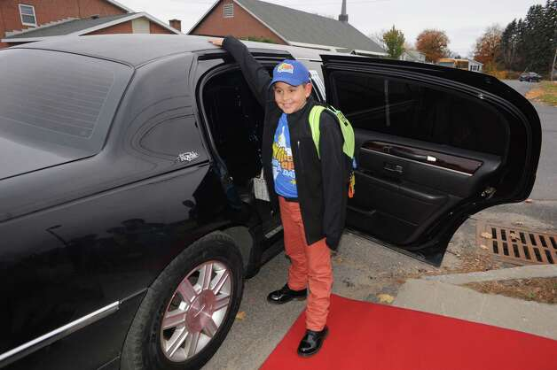 Nikos Johnson, center, a third grade student at Jefferson Elementary School gets picked up from school by limo with five of his friends after winning the First New York Federal Credit Union's Millionaire for the Day on Thursday Nov. 13, 2014 in Rotterdam, N.Y. First New York Federal Credit Union has been teaching thousands of area students for years to save their money through its KID$ (Keep Investing Dollars Savings) Program. To celebrate the studentsa€™ success, the credit union randomly selected a school banker to be treated like a Millionaire. As the Millionaire for the Day, Nikos Johnson and his classmates will be treated to a waiter-served lunch. In addition, Nikos and five of his friends will be picked up from Jefferson Elementary School at dismissal time and the red carpet will be rolled out treating them to a limousine ride to First New York Federal Credit Uniona€™s headquarters at 2 Wall Street, Albany where they will meet the President/CEO, Lucy Halstead and members of the Board of Directors, receive a personal tour of the credit union and return home via limousine at the end of the day. Mr. Joby Gifford, Principal at Jefferson Elementary School. Nikos, like many other students at Jefferson Elementary School make deposits each week from money they have earned by doing chores, receiving allowance and birthday money. Some students deposit money into their savings account from the soda bottles they help return, while others often find money on the ground. (Michael P. Farrell/Times Union) Photo: Michael P. Farrell / 00029474A