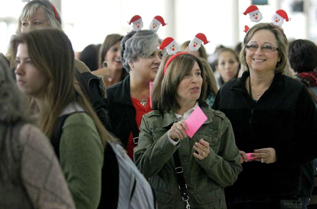 Wearing Santa headbands Brenda Elliott, left, of Richmond, Pam Labay, center, and Evelyn Labay, right, both of El Campo wait in line to enter the Nutcracker Market at NRG Center, Thursday, Nov. 13, 2014, in Houston.