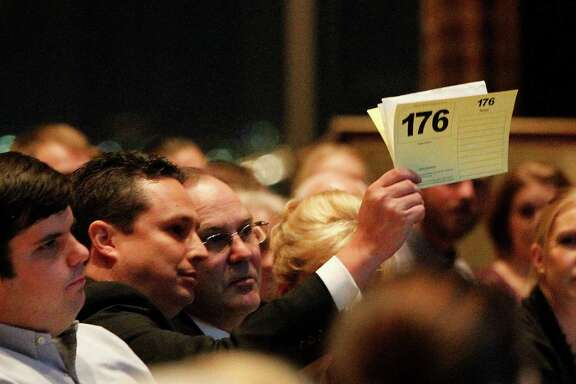 Daniel Moreno, the Petroleum Club's general manager, raises his bid card for the David Adickes tapestry that hangs in the ballroom.