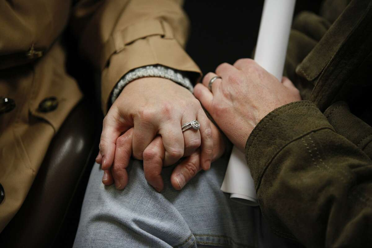 Topeka residents Tessy Best and Quinta Avance hold hands while waiting for their marriage application to be processed on Thursday, Nov. 13, 2014, at the Douglas County Courthouse, in Lawrence, Kan. Best is wearing an engagement ring that Avance gave her in April, but the two say that they made a commitment to each other 10 years ago. (AP Photo/The Lawrence Journal-World, Nick Krug)