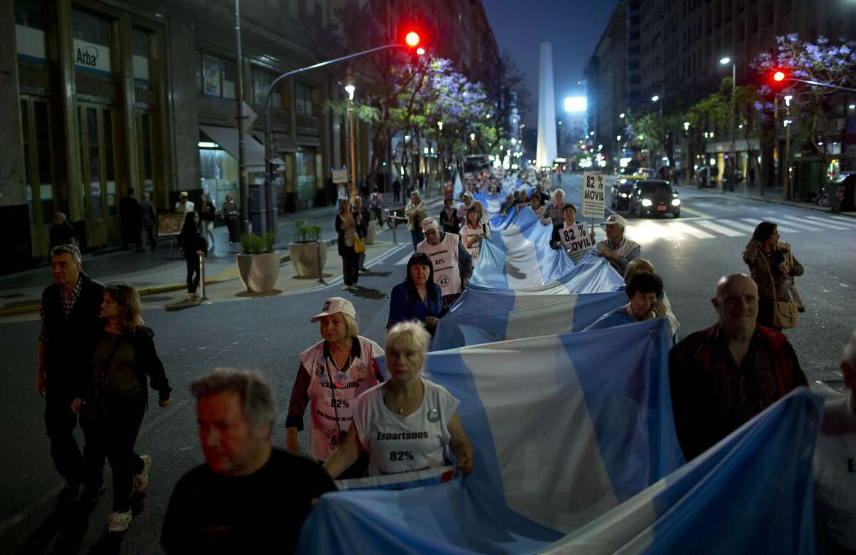 Demonstrators hold an Argentine flag as they head to Plaza de Mayo during a protest against the government of Argentina's President Cristina Fernandez in Buenos Aires, Argentina, Thursday, Nov. 13, 2014. (AP Photo/Natacha Pisarenko)