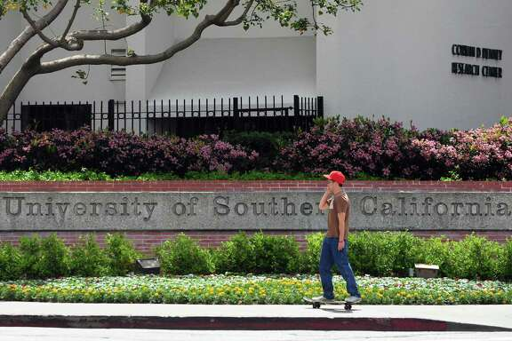A student rides his skateboard past an entrance to the University of Southern California (USC) campus in Los Angeles on April 11, 2012 in California. Two Chinese graduate students from the university were killed early April 11 in a shooting which could have been a failed carjacking in an area southwest of downtown Los Angeles, according to police. Los Angeles has a large Chinese and Chinese-American population, including many students, and certain areas of the city are known for frequent gun violence. AFP PHOTO/Frederic J. BROWN