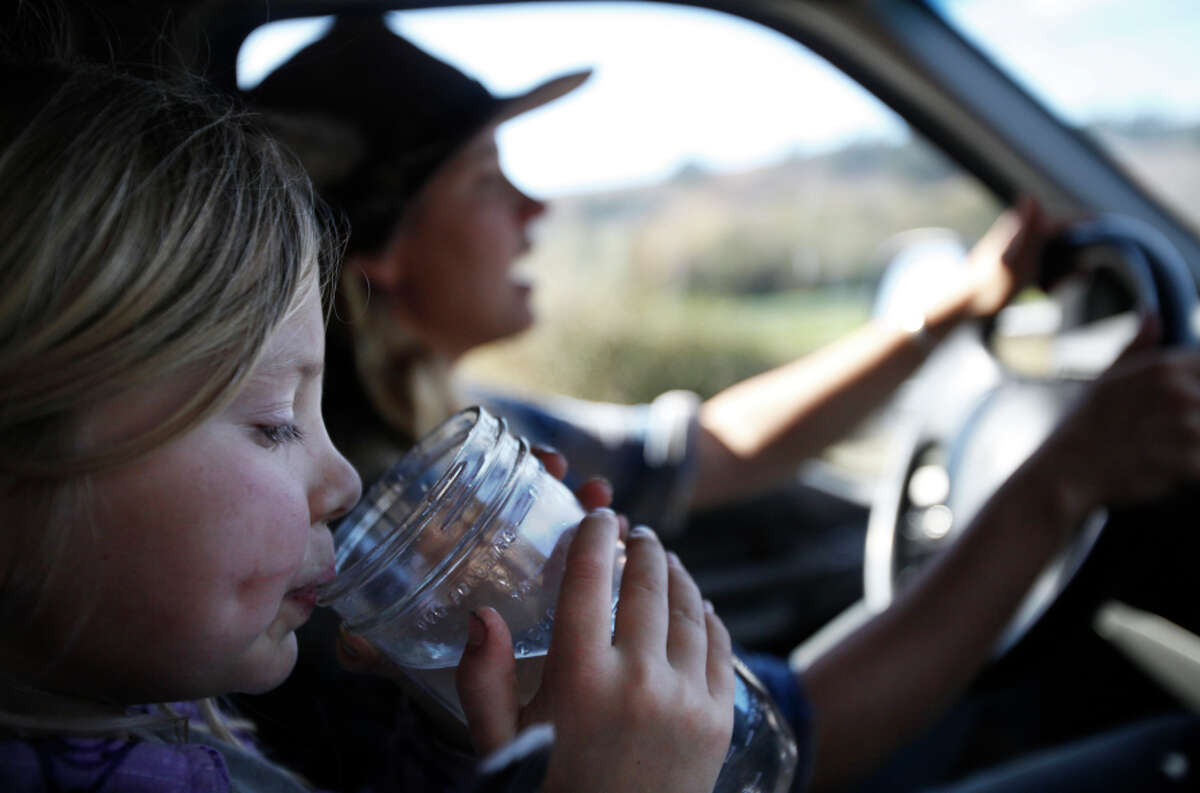 Six-year-old Quill Markegard sips water while her mother Doniga Markegard, drives the family back to their ranch.