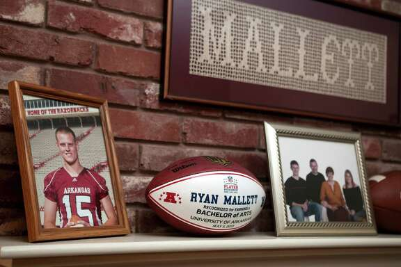 Photos and memorabilia from Ryan Mallet's time at the University of Arkansas sit on the mantle of the fireplace of his parents Jim and Debbie Mallet's home Monday, Nov. 10, 2014 in Texarkana, Ark.