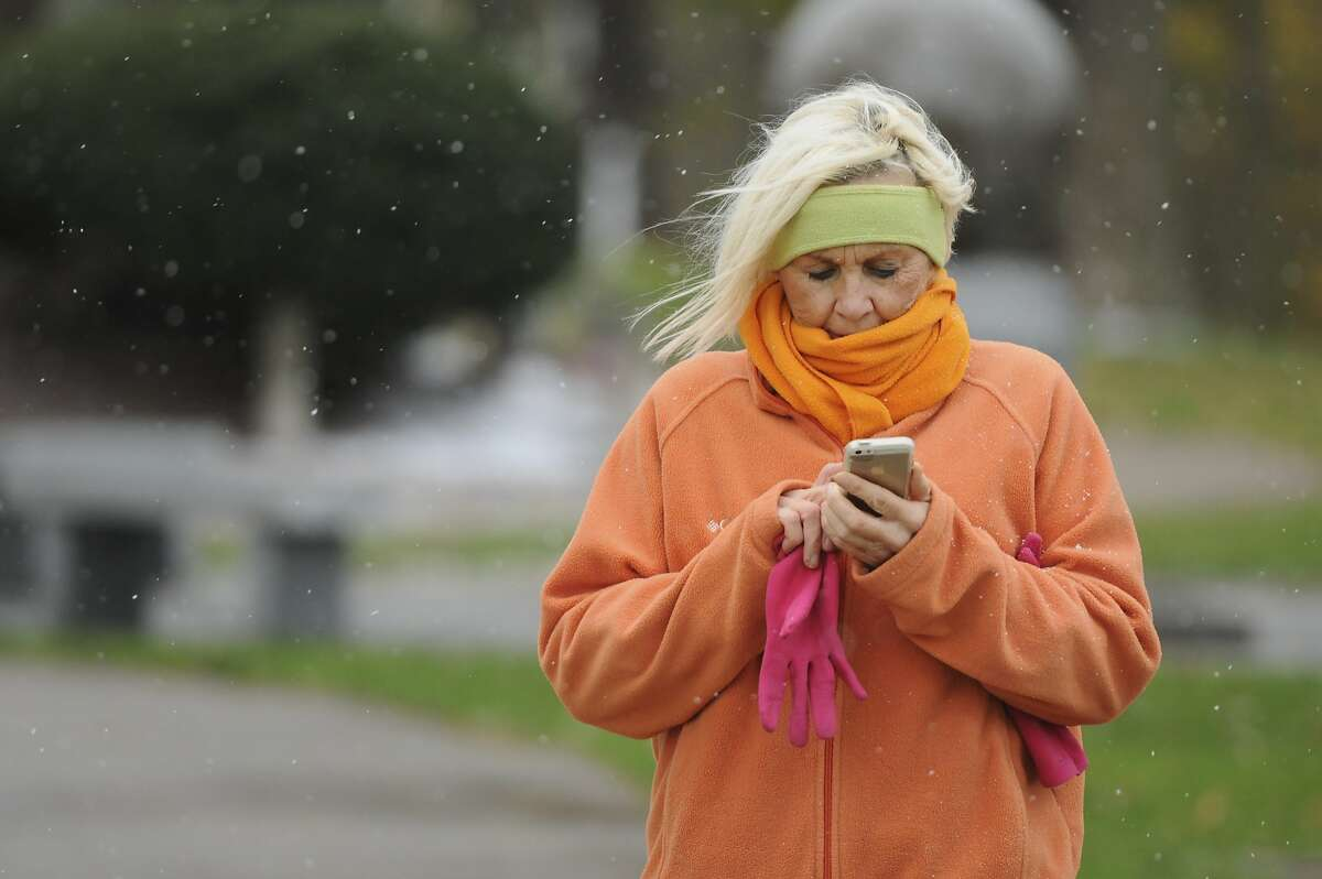 But my weather app says it's sunny! Snow flurries fall as Norleen LeClear checks her phone while out for a walk in St. Joseph, Mich., during an unseasonably early cold snap.