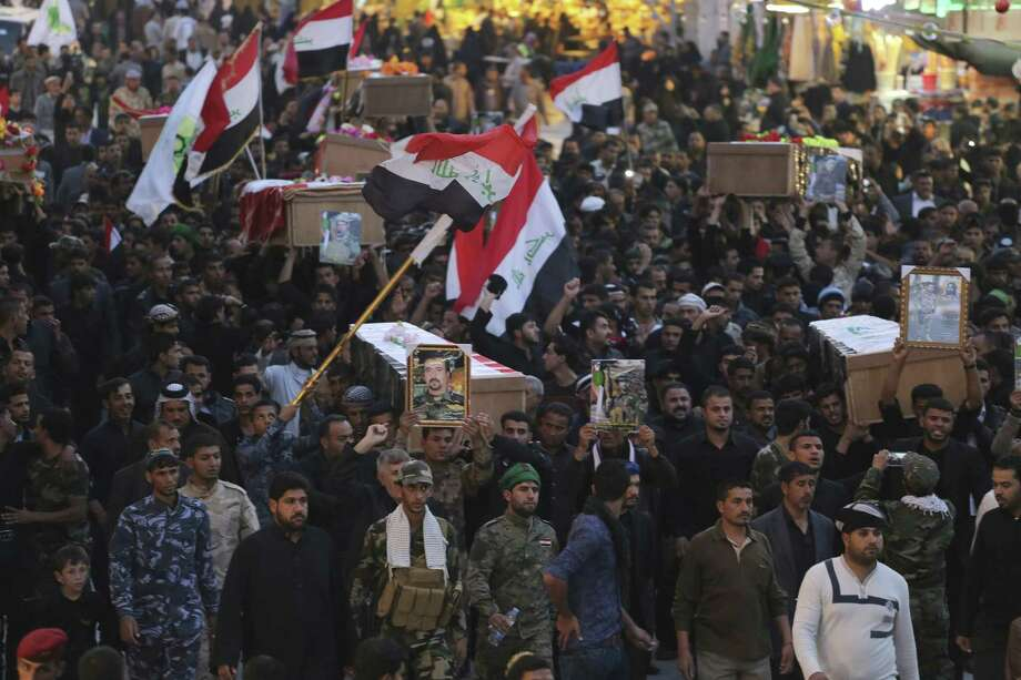Mourners carry the flag-draped coffins of 10 militia members of a Shiite Supreme Islamic Council, killed during clashes with Islamic State group in Diyala province, during a mass funeral in the Shiite holy city of Najaf, 100 miles south of Baghdad. Photo: Jaber Al-Helo / Associated Press / AP
