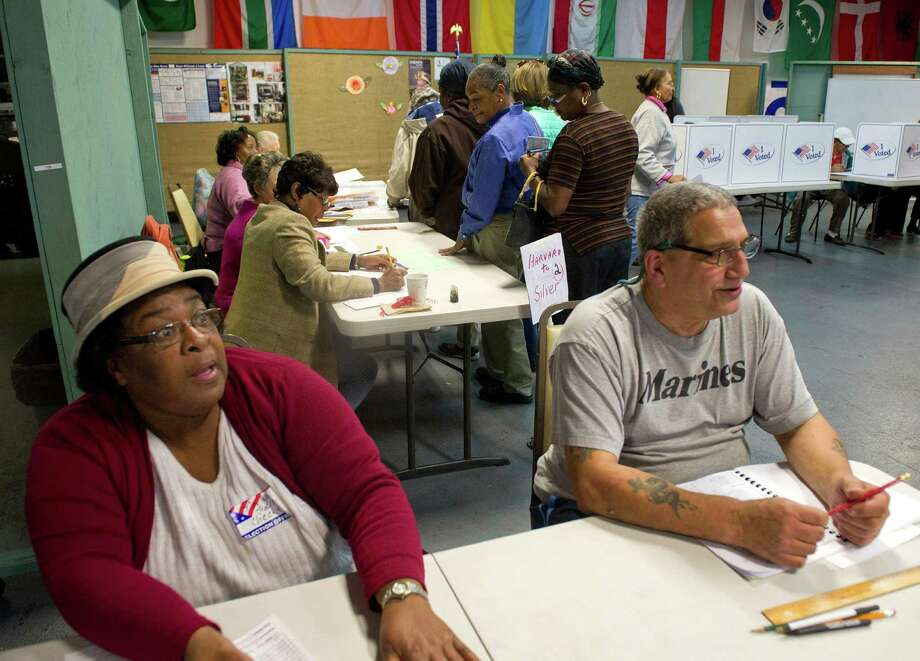 Poll workers wait for voters at Neighbor's Link in Stamford, Conn., on Tuesday, November 4, 2014. Photo: Lindsay Perry / Stamford Advocate