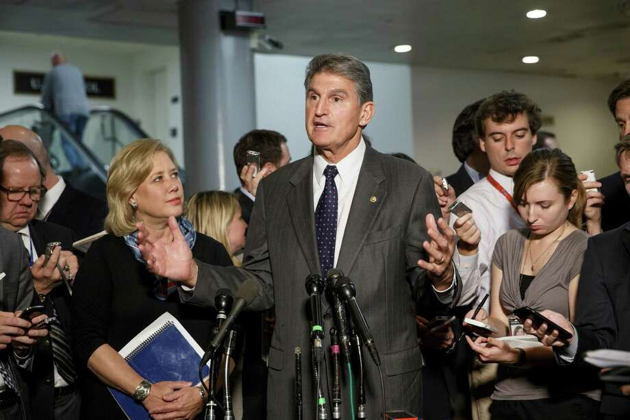 Sen. Mary Landrieu, D-La., chair of the Senate Energy Committee, left, listens as Sen. Joe Manchin, D-W. Va.,  a member of the committee, speaks to reporters about the new urgency to get congressional approval for the Canada-to-Texas Keystone XL pipeline, at the Capitol in Washington, Wednesday, Nov. 12, 2014. Three-term Democratic Sen. Mary Landrieu, facing an uphill fight to hold her seat in a Dec. 6 runoff, called for a vote on approving the pipeline. President Barack Obama has delayed a decision on the project that is opposed by environmental groups. Republicans insist that it will create jobs. (AP Photo/J. Scott Applewhite) Photo: J. Scott Applewhite / Associated Press / AP