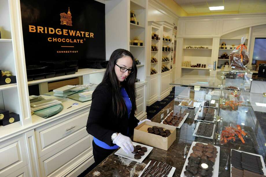 Brianna Smith of Bethel arranges chocolates in a display at the new Bridgewater Chocolates retail store on Federal Road in Brookfield, Conn., Friday, Nov. 14, 2014. Photo: Carol Kaliff / The News-Times
