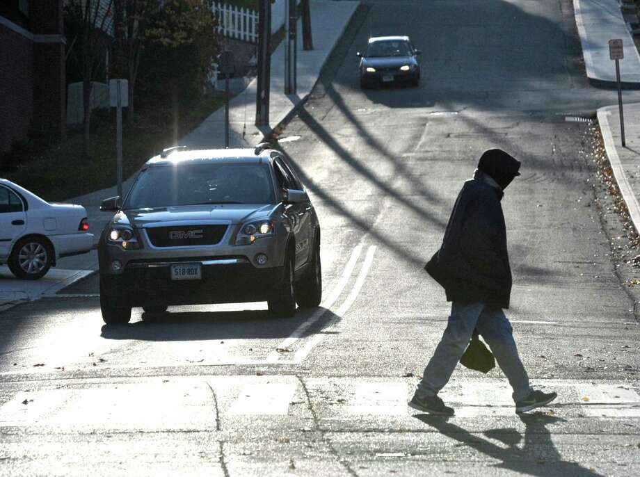 A pedestrian crosses Library Place, by Main Street, in Danbury, Conn, on Friday afternoon, November 14, 2014. Photo: H John Voorhees III / The News-Times