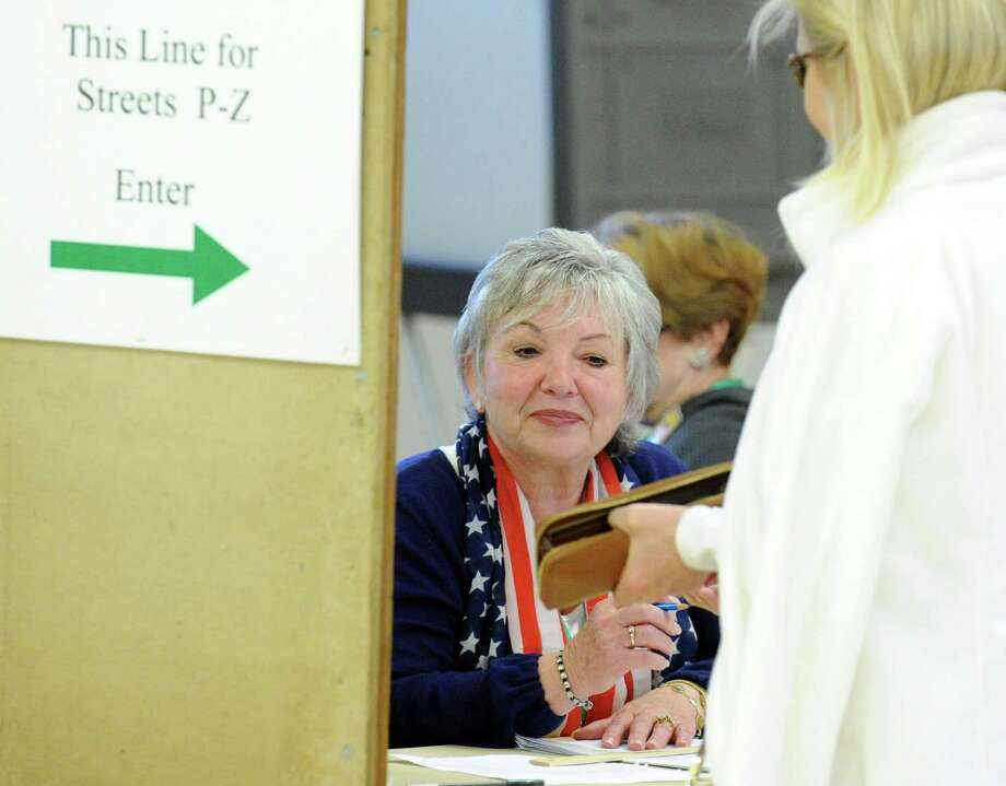 Assistant Registrar of Voters, Lucy Ann Macaluso, at center, checks the identification of a voter during voting at the Western Greenwich Civic Center in the Glenville section of Greenwich, Conn., Tuesday, Nov. 4, 2014. Photo: Bob Luckey / Greenwich Time