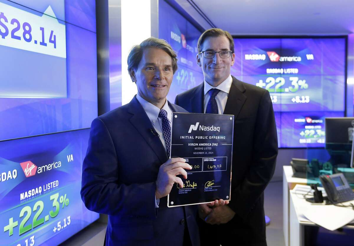 David Cush, left, President & CEO of Virgin America, poses for photos with Nasdaq CEO Robert Greifeld and his IPO certificate after Virgin America began trading at the Nasdaq MarketSite, in New York, Friday, Nov. 14, 2014. The shares opened at $27 - $4 higher than the price that the airline set - and then jumped as high as $29.74 within about an hour of the opening bell. (AP Photo/Richard Drew)
