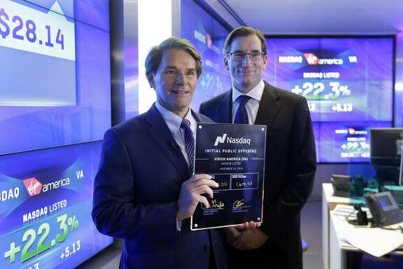 David Cush, left, President & CEO of Virgin America, poses for photos with Nasdaq CEO Robert Greifeld and his IPO certificate after Virgin America began trading at the Nasdaq MarketSite, in New York, Friday, Nov. 14, 2014. The shares opened at $27 — $4 higher than the price that the airline set — and then jumped as high as $29.74 within about an hour of the opening bell. (AP Photo/Richard Drew)