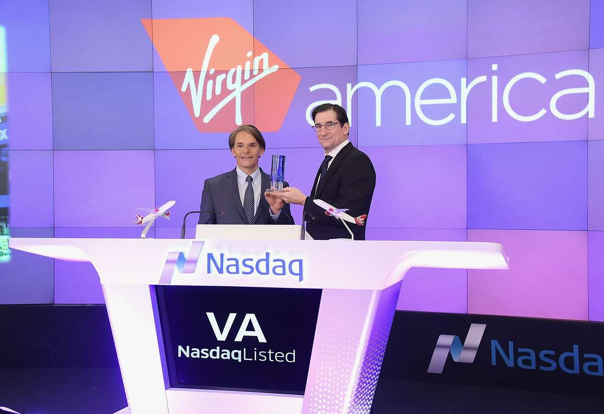 NEW YORK, NY - NOVEMBER 14: Virgin America President and CEO David Cush (L) and Nasdaq CEO Robert Greifeld hold up the Nasdaq Opening Bell Crystal before ringing the opening bell in celebration of the company's initial public offering on November 14, 2014 in New York City. Virgin America is a US airline that raised $307 million by offering 13.3 million shares at $23 and lists on the NASDAQ under the symbol VA. (Photo by Michael Loccisano/Getty Images)