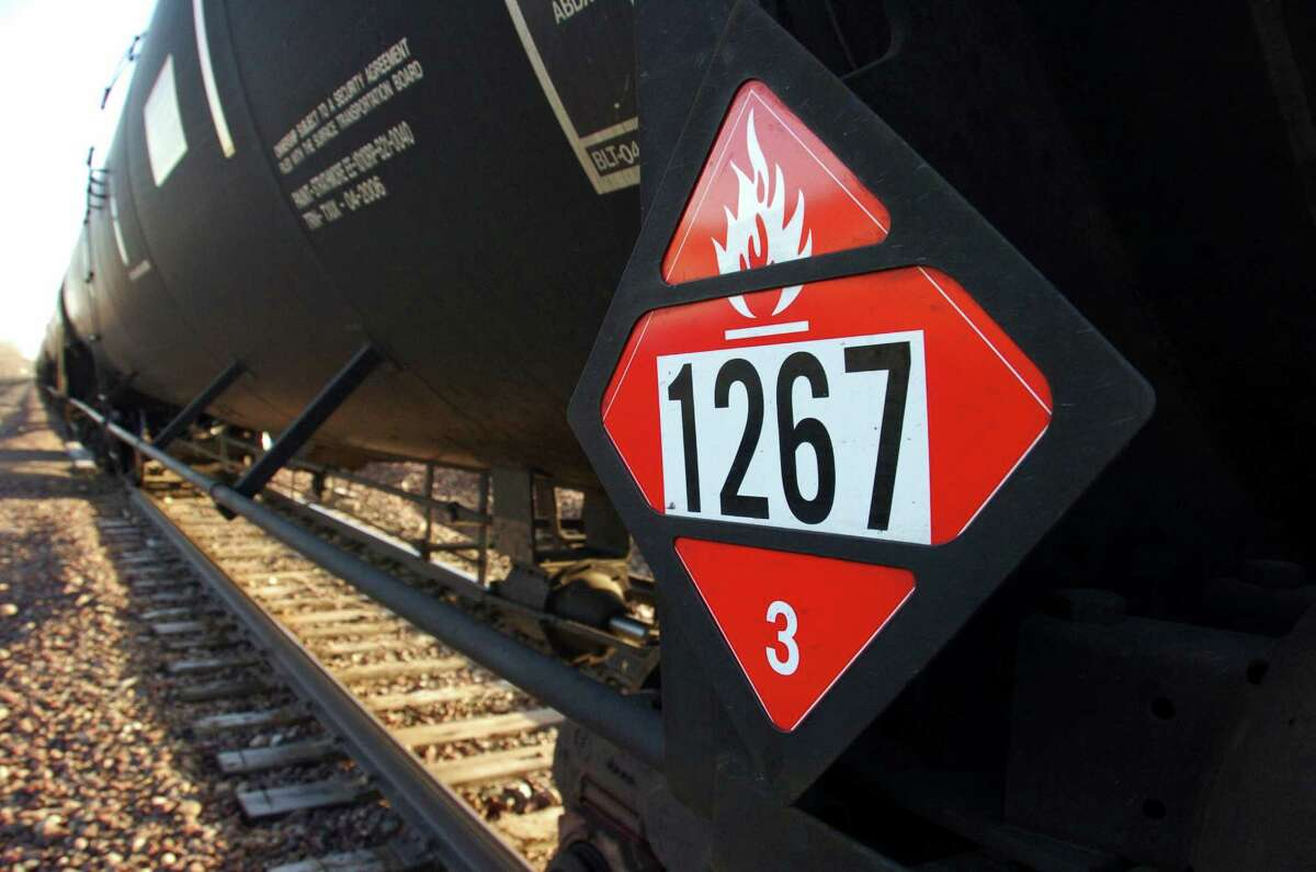 FILE - This Nov. 6, 2013 file photo shows a warning placard on a tank car carrying crude oil near a loading terminal in Trenton, N.D. Thousands of older rail tank cars that carry crude oil would be phased out within two years under regulations proposed in response to a series of fiery train crashes over the past year. The oil industry's lead trade group released new standards on Thursday, Sept. 25, 2014, for testing and classifying crude shipped by rail after prior shipments were misclassified, including a train that derailed in Canada and killed 47 people. (AP Photo/Matthew Brown, File)
