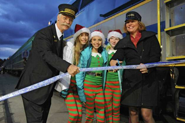 Saratoga Springs Mayor Joanne Yepsen, right,  cuts a ribbon with, from right, the Polar Express Conductor, Sophie Leidig, 12, of Saratoga Springs, Gianna Cognetti, 12, of Ballston Spa, and Kristen Shinebarger, 12, of Ballston Spa, to mark the official opening of The Polar Express train ride at the Saratoga Train Depot on Friday, Nov. 14, 2014 in Saratoga Springs, N.Y.  (Lori Van Buren / Times Union) Photo: Lori Van Buren / 00029477A