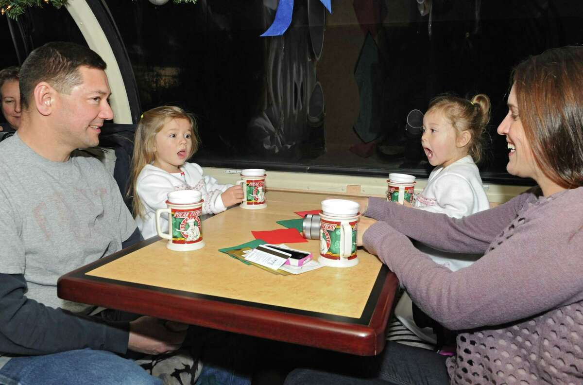 From left, Mike McDade of Baldwinsville, sits with his children Sophia, 3, Chloe, 2, and his wife Julie on the Polar Express train on the official opening night of the train ride at the Saratoga Train Depot on Friday, Nov. 14, 2014 in Saratoga Springs, N.Y. (Lori Van Buren / Times Union)