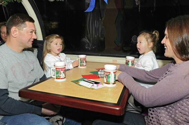 From left, Mike McDade of Baldwinsville, sits with his children Sophia, 3, Chloe, 2, and his wife Julie on the Polar Express train on the official opening night of the train ride at the Saratoga Train Depot on Friday, Nov. 14, 2014 in Saratoga Springs, N.Y.  (Lori Van Buren / Times Union) Photo: Lori Van Buren / 00029477A