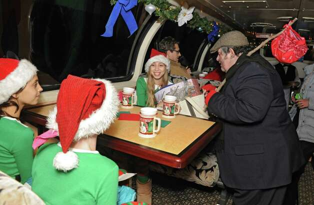 From counter clockwise, Homer the hobo talks to Sophie Leidig, 12, of Saratoga Springs, Gianna Cognetti, 12, of Ballston Spa, and Kristen Shinebarger, 12, of Ballston Spa, during the official opening of The Polar Express train ride at the Saratoga Train Depot on Friday, Nov. 14, 2014 in Saratoga Springs, N.Y.  (Lori Van Buren / Times Union) Photo: Lori Van Buren / 00029477A