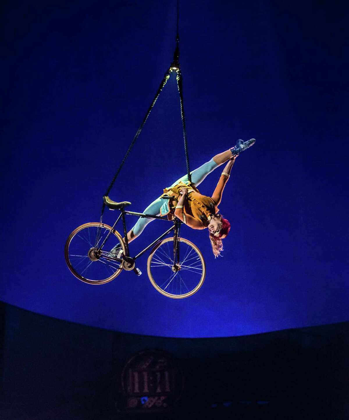 Anne Weissbecker performs suspended in the aerial bicycle act in Cirque du Soleil's