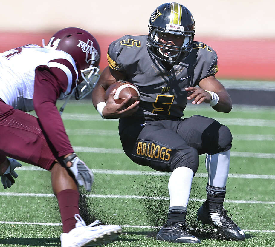 Texas Lutheran running back Marquis Barrolle uses a quick stop to get around a Trinity tackler at the TLU's new Bulldog Stadium in Seguin on Nov. 1, 2014. Photo: Tom Reel /San Antonio Express-News