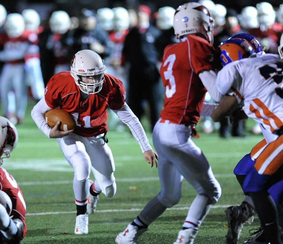 As he gets a block from teammate Austin Longi (#3), right, Greenwich running back Ryan Pasquali (#11), left, finds the hole to score a second quarter touchdown during the high school football game between Greenwich High School and Danbury High School at Greenwich, Conn., Friday night, Nov. 14, 2014. Photo: Bob Luckey / Greenwich Time