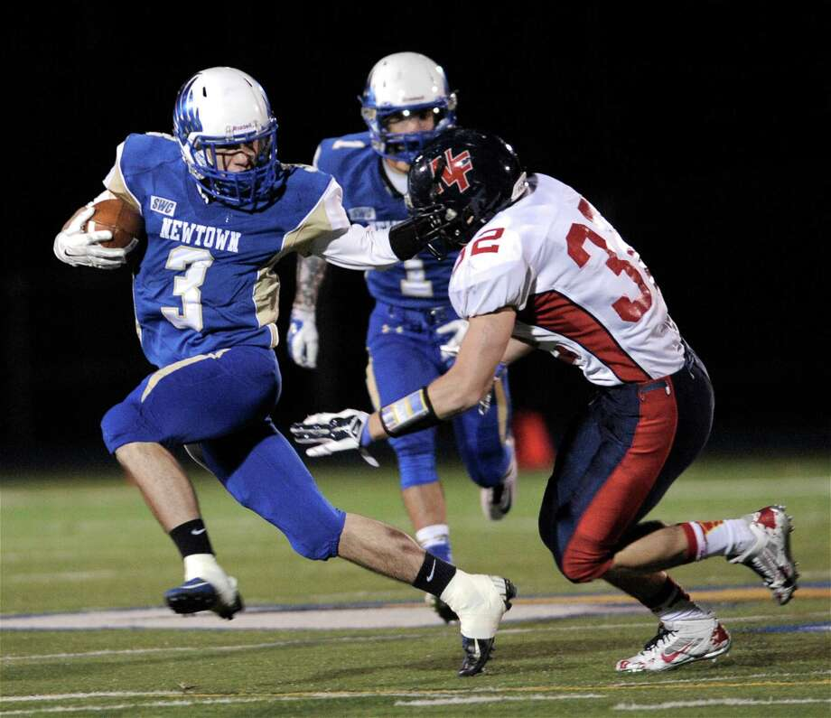 Newtown's Troy Frangione (3) tries to go outside New Fairfield's Trevor Schretzenmayer (32) during the SWC football game between New Fairfield and Newtown high schools, played at Newtown High School, Newtown, Conn, on Friday night, November 14, 2014. Photo: H John Voorhees III / The News-Times