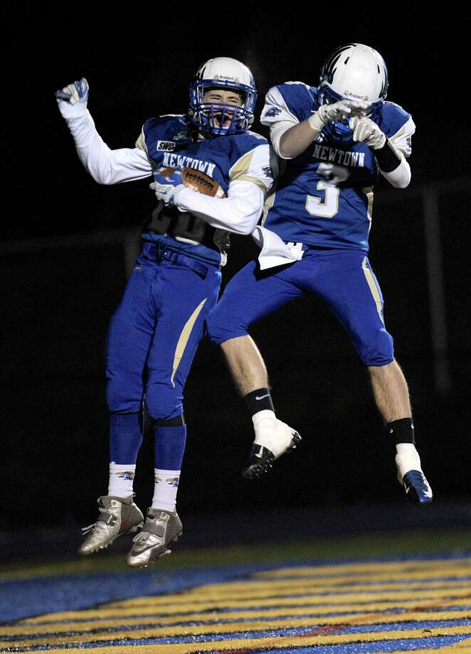Newtown's Michael Doyle (20) and Troy Frangione (3) celebrate a touchdown by Doyle during the SWC football game between New Fairfield and Newtown high schools, played at Newtown High School, Newtown, Conn, on Friday night, November 14, 2014. Photo: H John Voorhees III / The News-Times