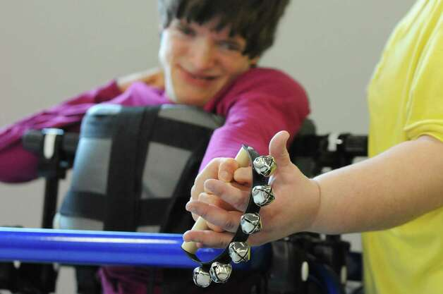 Margaret Mary Whelan gets help shaking bells from Dawn Bruno during rehearsal for a collaborative dance performance on Thursday, Nov. 13, 2014, at Albany Academy for Girls  in Albany, N.Y. Ellen Sinopoli Dance Co. and dance students from Albany Academy for Girls performed with severely disabled adults from the Center for Disability Services. (Cindy Schultz / Times Union) Photo: Cindy Schultz / 00029467A