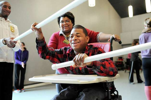 Ray Kirkley, center, pushes up a barrier with assistance from Tess Breedlove during rehearsal for a collaborative dance performance on Thursday, Nov. 13, 2014, at Albany Academy for Girls  in Albany, N.Y. Ellen Sinopoli Dance Co. and dance students from Albany Academy for Girls performed with severely disabled adults from the Center for Disability Services. (Cindy Schultz / Times Union) Photo: Cindy Schultz / 00029467A