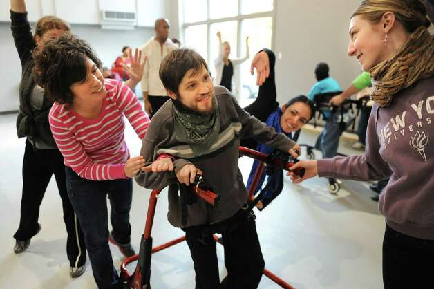Joseph Ricciardon, center, gets assistance from Tammy Czarnecki, left, as they interact with dancers during rehearsal for a collaborative dance performance on Thursday, Nov. 13, 2014, at Albany Academy for Girls  in Albany, N.Y. Ellen Sinopoli Dance Co. and dance students from Albany Academy for Girls performed with severely disabled adults from the Center for Disability Services. (Cindy Schultz / Times Union) Photo: Cindy Schultz / 00029467A
