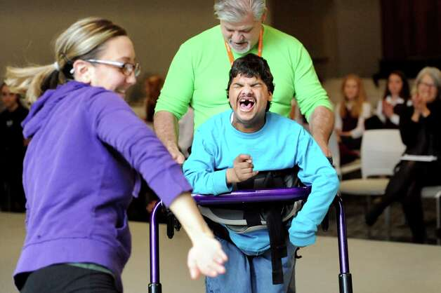 Devin Whelan, center, with assistance from Eugene Kupiec Jr., reacts as Sara Senecal dances past him during rehearsal for a collaborative dance performance on Thursday, Nov. 13, 2014, at Albany Academy for Girls  in Albany, N.Y. Ellen Sinopoli Dance Co. and dance students from Albany Academy for Girls performed with severely disabled adults from the Center for Disability Services. (Cindy Schultz / Times Union) Photo: Cindy Schultz / 00029467A