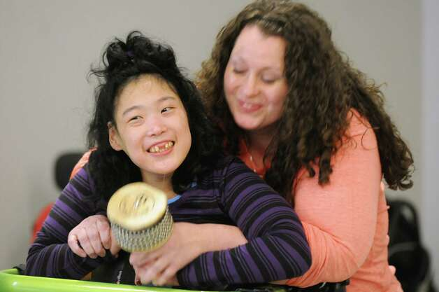 Sarah Hillicoos, left, gets assistance from Brittany Haessig as she makes music during rehearsal for a collaborative dance performance on Thursday, Nov. 13, 2014, at Albany Academy for Girls  in Albany, N.Y. Ellen Sinopoli Dance Co. and dance students from Albany Academy for Girls performed with severely disabled adults from the Center for Disability Services. (Cindy Schultz / Times Union) Photo: Cindy Schultz / 00029467A