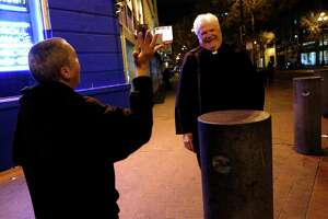 Night Minister the Rev. Lyle Beckman laughs on Market Street with a woman whom he regularly crosses paths with during his nightly shift on the streets.