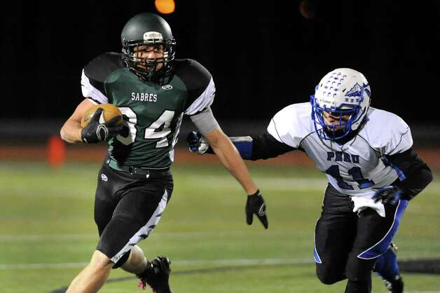 Schalmont's Dalton Cooke, left, carries the ball as Peru's Ryan Lovely defends during their Class B state quarterfinal football game on Friday, Nov. 14, 2014, at Shenendehowa High in Clifton Park, N.Y. (Cindy Schultz / Times Union) Photo: Cindy Schultz / 00029471A