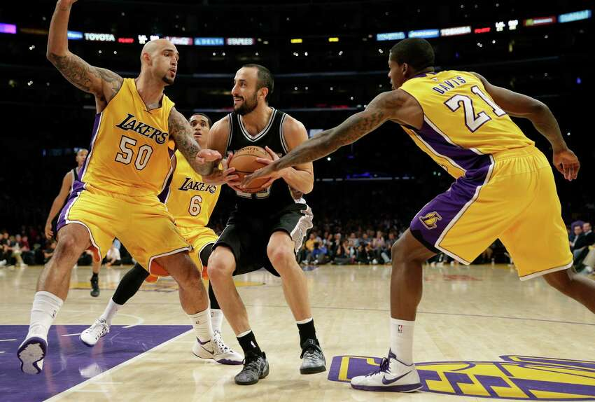 San Antonio Spurs' Manu Ginobili, center, of Argentina, is defended by Los Angeles Lakers' Robert Sacre, left, and Ed Davis during the first half of an NBA basketball game Friday, Nov. 14, 2014, in Los Angeles. (AP Photo/Jae C. Hong)