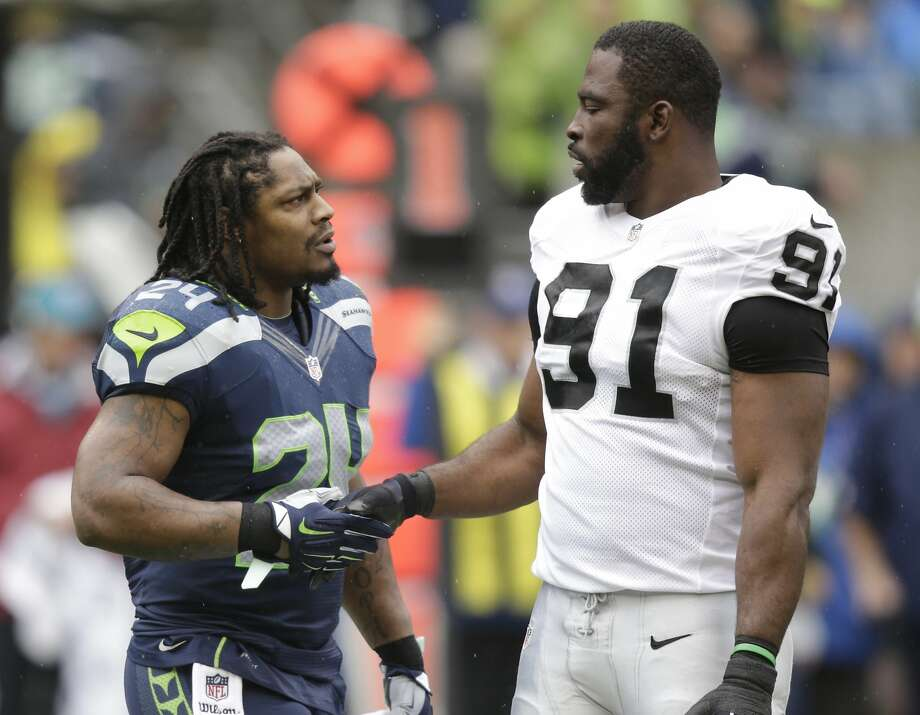 Seattle Seahawks' Marshawn Lynch, left, greets Oakland Raiders' Justin Tuck before an NFL football game, Sunday, Nov. 2, 2014, in Seattle. (AP Photo/Stephen Brashear) Photo: Stephen Brashear, Associated Press